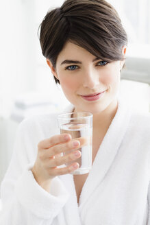 Germany, Bavaria, Munich, Portrait of young woman holding water glass, close up - SPOF000379