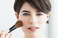 Germany, Bavaria, Munich, Young woman using blusher brush, close up - SPOF000409