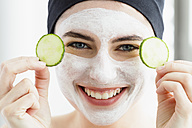 Germany, Bavaria, Munich, Portrait of young woman with cucumber mask, close up - SPOF000414