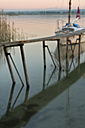 Germany, Boat next to jetty reflecting in water at Lake Constance - SH000683
