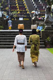 Indonesia, Women carrying basket on head and walking at Pura Penataran Agung temple - AM000053