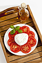 Buffalo mozzarella with basil, tomatoes and bottle of olive oil on plate, close up - CSF019168