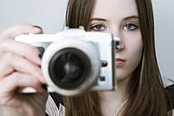 Portrait of Teenage girl holding digital camera - JAT000008