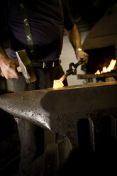 Blacksmith working with hammer at anvil - CNF000048