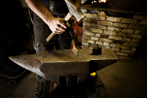 Blacksmith working with hammer at anvil - CNF000051