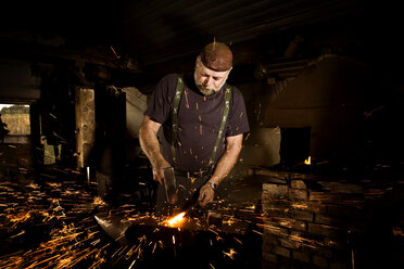 Blacksmith working with hammer at anvil surrounded by sparks - CNF000065