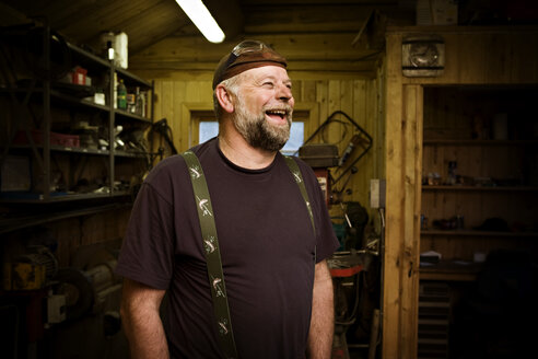 Laughing craftsman in his workshop - CNF000077