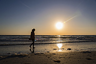 USA, Florida, Indian Rocks Beach, Mature woman walking on beach during sunset - ABAF000839
