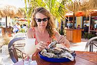 USA, Florida, Miami, Mature woman eating fresh raw oysters, close up - ABA000860