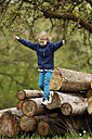 Germany, Baden Wuerttemberg, Girl jumping from wooden logs - SLF000121