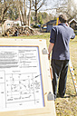 Germany, Brandenburg, Men surveying at construction site - FK000186