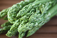 Germany, Saxony, Green asparagus on wooden table, close up - JTF000399