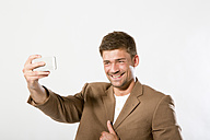 Young man taking picture with smartphone, close up - MAEF006810