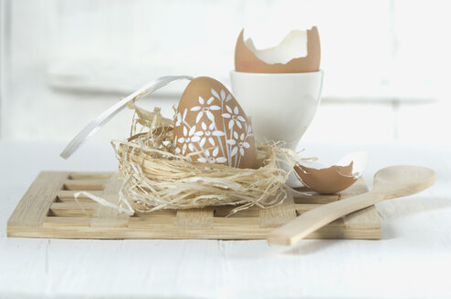 Painted easter egg in straw nest with wooden spoon on white background - ASF004972