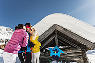 Austria, Salzburg, Young man and young women standing in front of alpine hut - HH004630