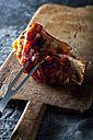 Grilled knuckle of pork with fork on chopping board, close up - CSF019326