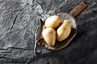 Raw potatoes on wooden spoon, close up - CSF019394