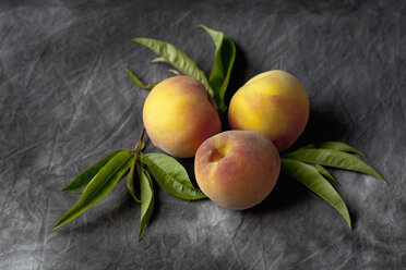 Peaches with leaves on black textile, close up - CSF019362