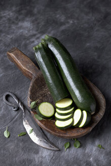 Courgette on wooden spoon with knife on black textile, close up - CSF019357