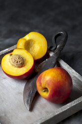 Peaches with knife on tray, close up - CSF019407