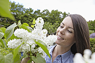 Germany, Cologne, Young woman holding tree blossom, smiling - RHYF000390