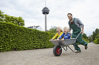 Germany, Cologne, Father carrying son in wheelbarrow, smiling - RHYF000380