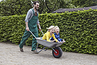 Germany, Cologne, Father carrying son in wheelbarrow, smiling - RHYF000377