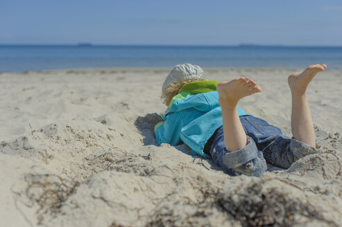 Germany, Mecklenburg Western Pomerania, Boy relaxing on sand at baltic sea - MJF000170