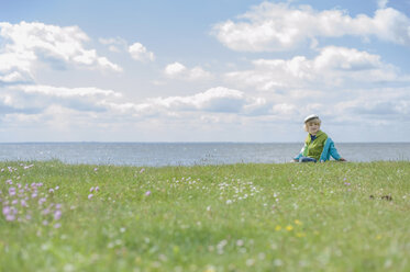 Germany, Mecklenburg Vorpommern, Boy sitting on grass at baltic sea - MJF000179