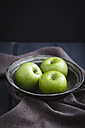 Bowl of green apples on wooden table, close up - ECF000184