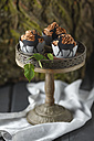 Cupcakes topped with chocolate buttercream and wrappers decorated with deers on cake stand - ECF000181