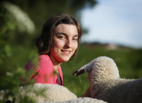 Germany, Baden Wuerttemberg, Portrait of teenage girl with group of lambs sitting on meadow, smiling - SLF000129