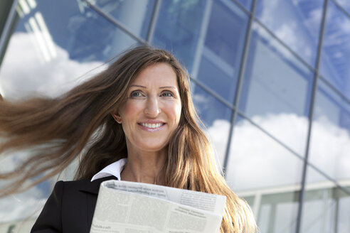 Germany, Berlin, Businesswoman holding newspaper, smiling - FKIF000004