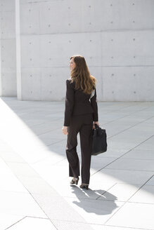 Germany, Berlin, Businesswoman walking with briefcase - FKIF000014