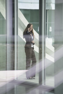 Germany, Berlin, Portrait of businesswoman talking on smart phone, smiling - FKIF000028