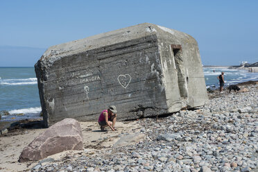Denmark, View of mature woman collecting shells at Bunker ruin - HWO000042