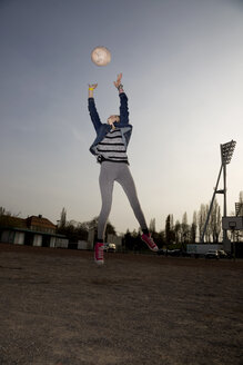 Germany, Berlin, Teenage girl catching football - TKF000137