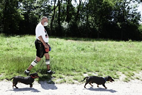 Germany, Bavaria, Munich, Senior man walking with dogs - ED000028
