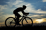Germany, Mature man riding bicycle in sunset - STS000013