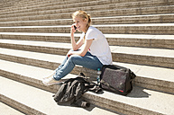Germany, Berlin, Young woman sitting on stairs and talking on mobile phone, smiling - BFR000233