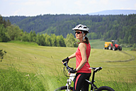 Germany, Mid adult woman standing with bicycle in forest - VT000010