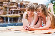Young women using digital tablet at swimming pool, smiling - ABAF000940