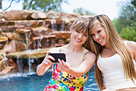 Young women using smart phone to take picture at swimmin pool, smiling - ABAF000885