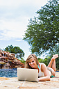 Young woman using laptop at swimming pool, smiling - ABAF000879