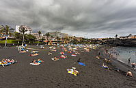 Spain, People relaxing at black sand beach - AM000360