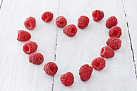 Heart shaped with raspberries on wooden table, close up - KSW001087