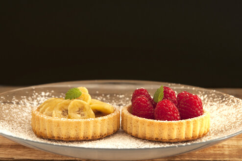 Banana and raspberry tartlets on plate, close up - OD000054