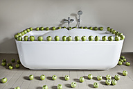 Bathtub filled with green apples in bathroom - FMKYF000294
