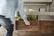 Mature man opening drawer with herbs - FMKYF000441
