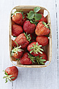 Box of strawberries on wooden table, close up - KSW001130